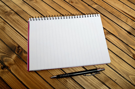 Empty notebook and pen on table Stock Photo