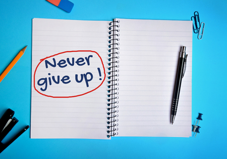 give up: Never give up word writing on notebook Stock Photo