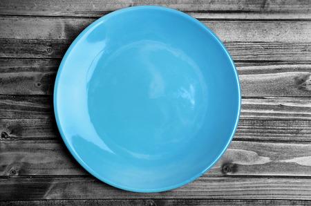 azul turqueza: Plato azul vac�o en la mesa de madera de color gris Foto de archivo