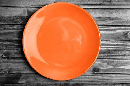 Empty orange plate on wooden table Imagens