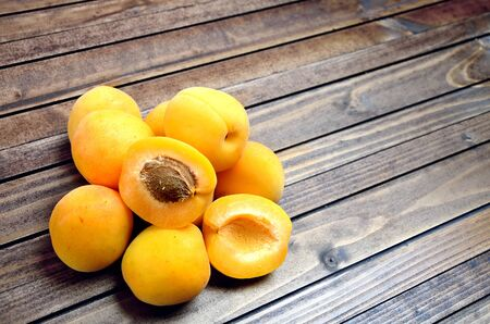apricot kernels: Heap of apricots fruit on wooden table Stock Photo