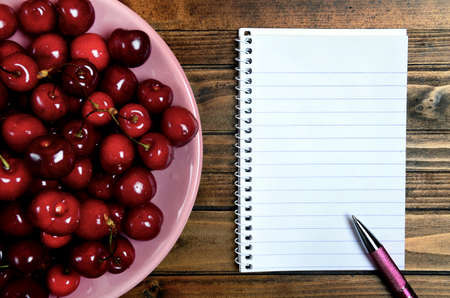 fruit plate: Plate with cherries fruit and notepad on table