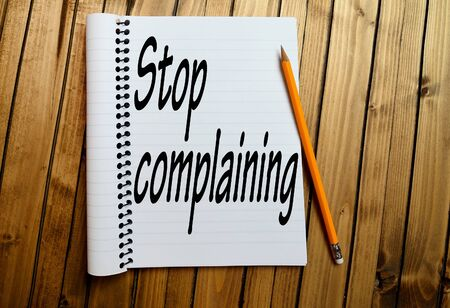 complaining: Stop complaining word on notepad Stock Photo