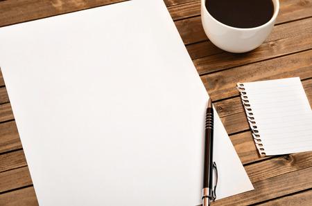 boligrafos: papel blanco con una taza de café en la mesa de madera Foto de archivo