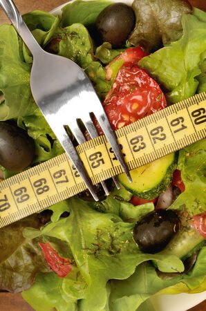 nutrition health: Vegetable salad with centimeter and fork