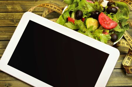 centimeter: Tablet with vegetable salad and centimeter on table