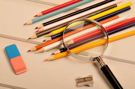 group search: Colorful pencil with magnifying glass on gray wooden table