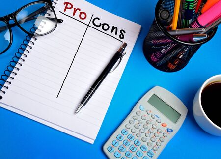 pro: Pro Cons word on notebook on blue background