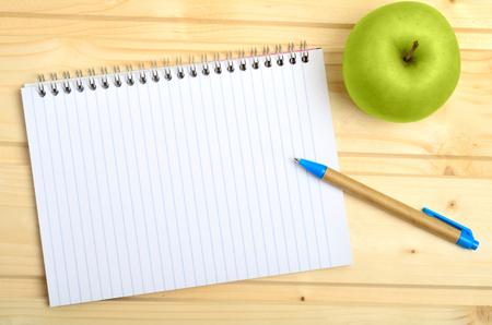 papeles oficina: Cuaderno con la pluma y las manzanas de mesa de madera Foto de archivo