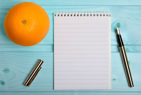 weightloss plan: Notebook with orange fruit and pen on table
