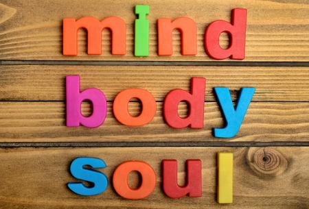 terapia psicologica: Colorido palabra Mind Body Soul en mesa de madera