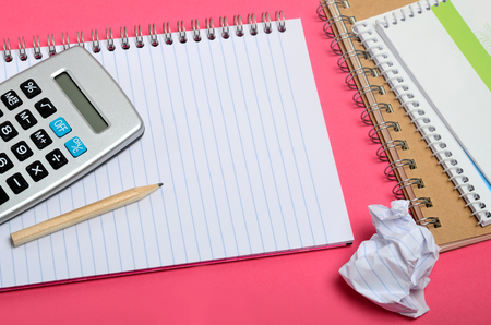 background stationary: Notebook with calculator on pink background