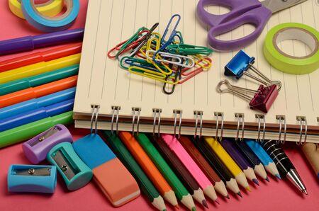 utiles escolares: Fuentes de escuela en fondo de color rosa