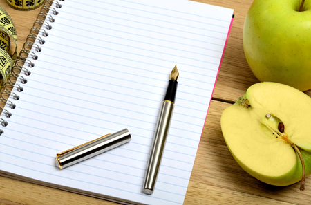 centimeter: Open notebook with apple fruit and centimeter on table Stock Photo