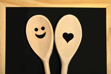 cooking utensil: Two lovely wooden spoon on blackboard
