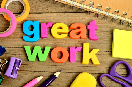 great: Colorful Great word with office supply on wooden table Stock Photo