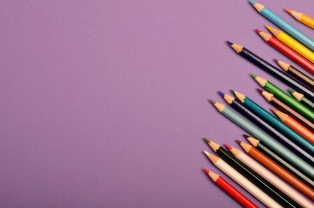 brown background: Many colorful pencils on purple background
