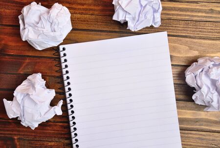crinkled: Notebook with crinkled paper on wooden table Stock Photo