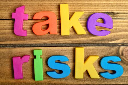 unafraid: Take risks word on wooden table