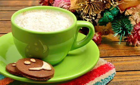 flower shape: Cup of cappuccino with cocoa biscuits on wooden table