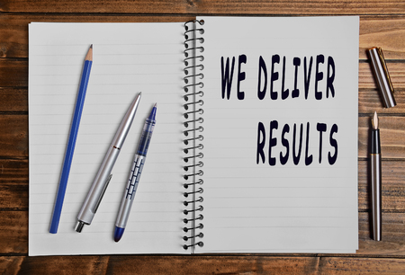 deliver: We deliver results text on notebook Stock Photo