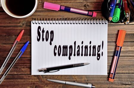 complaining: Stop complaining written on notebook Stock Photo