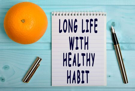 habit: Long life with healthy habit words on notebook