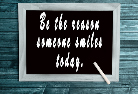 reason: Be the reason someone smiles today text on chalkboard Stock Photo