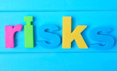 risky situation: Risks word on blue wooden table
