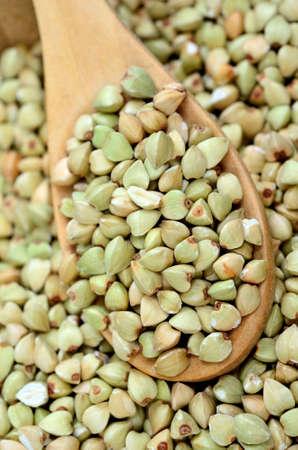 caloric: Healthy green buckwheat in a wooden spoon Stock Photo