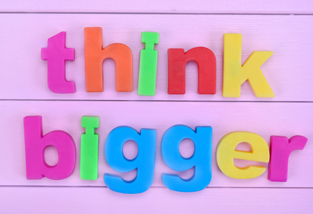 bigger: Words Think Bigger on pink wooden table