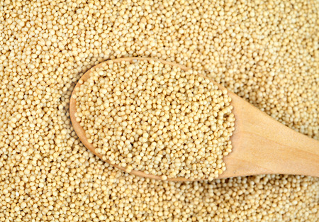 Wooden spoon with amaranth seed on background