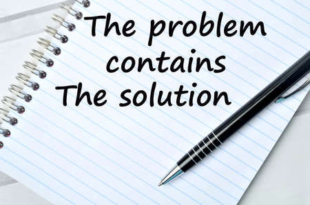 contains: The words The problem contains the solution on notebook Stock Photo