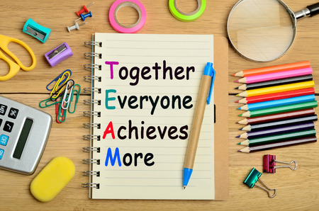 achieves: The words Together Everyone Achieves More on notebook