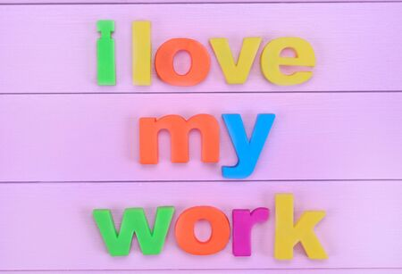 employment elementary school: The colorful words I love my work on pink table Stock Photo