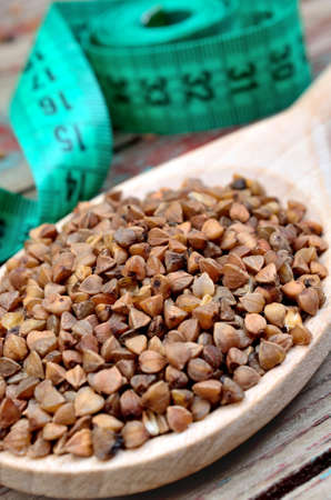 groats: Buckwheat groats in a wooden spoon and centimeter