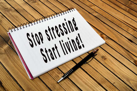 stressing: The words Stop stressing Start living on notebook closeup