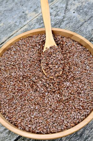 flaxseed: Flaxseed in a bamboo bowl on rustic wooden table Stock Photo