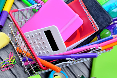 Shopping cart with objects school on table