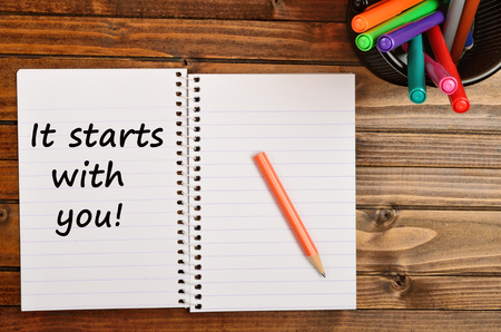 It starts with you words on notebook page Stock Photo