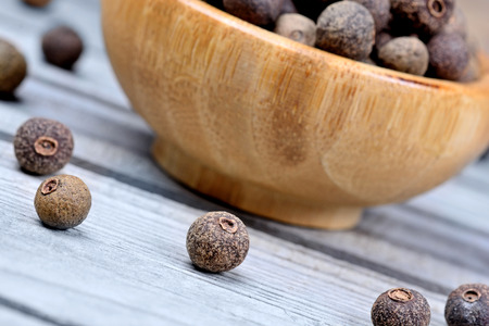 Bowl with allspice on blue wooden table Stock Photo
