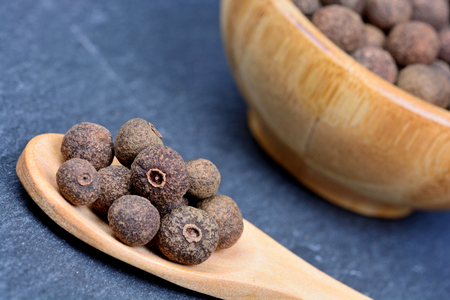 allspice: Allspice in a spoon and bowl on slate Stock Photo