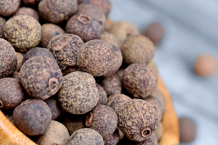 allspice: Bowl with allspice on blue wooden table Stock Photo