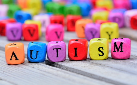 Autism word on wooden table Imagens