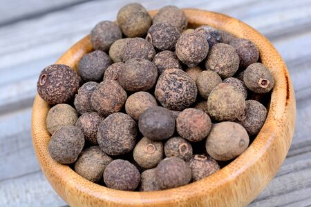 Allspice in a bamboo bowl on wooden table Stock Photo
