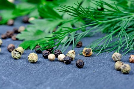 Peppercorns with dill and parsley on slate Stock Photo