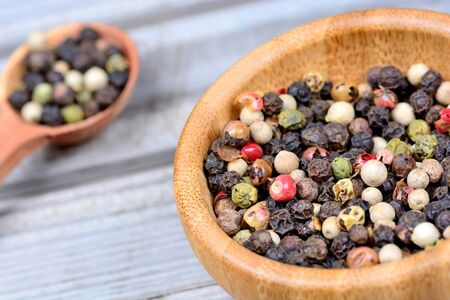 Colorful peppercorns in a bowl and spoon on table