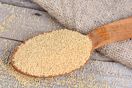 Amaranth seeds in a wooden spoon on table