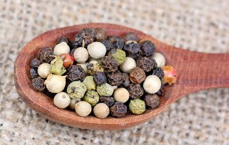 Colorful peppercorns in a wooden spoon on table