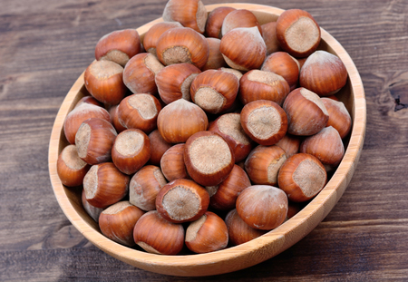 Hazelnuts in a bowl on wooden background Stock Photo